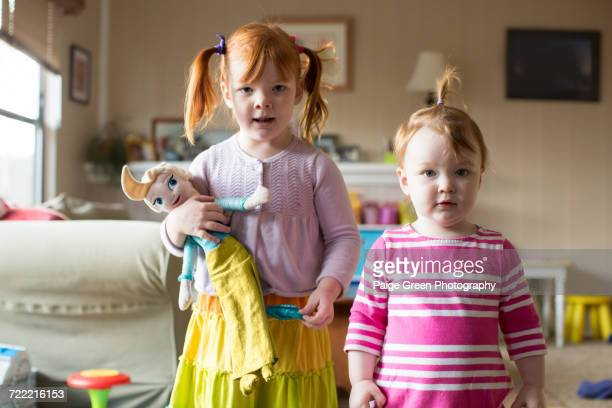 Portrait of two young sisters, older sister holding doll