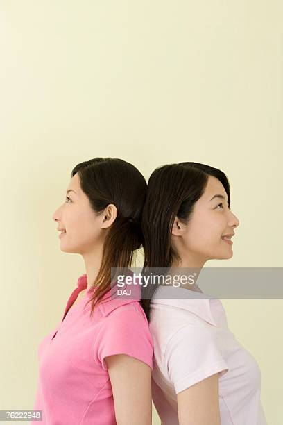 Portrait of Two Young Twin Sisters Back to Back, Smiling, Side View