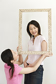 Portrait of Two Young Twin Sisters, Holding and Looking Through a Picture Frame, Smiling, Front View, Rear View