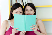 Portrait of Two Young Twin Sisters Reading a Book, Smiling, Front View