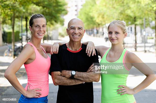 Portrait of two young women and trainer in park