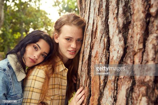 Portrait of two young women leaning against tree trunk