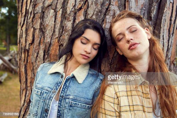 Portrait of two young women leaning against tree trunk with eyes closed