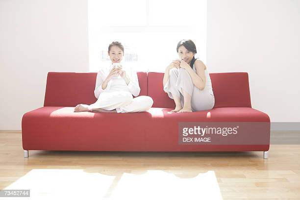 Portrait of two young women sitting on a couch and holding cups of coffee