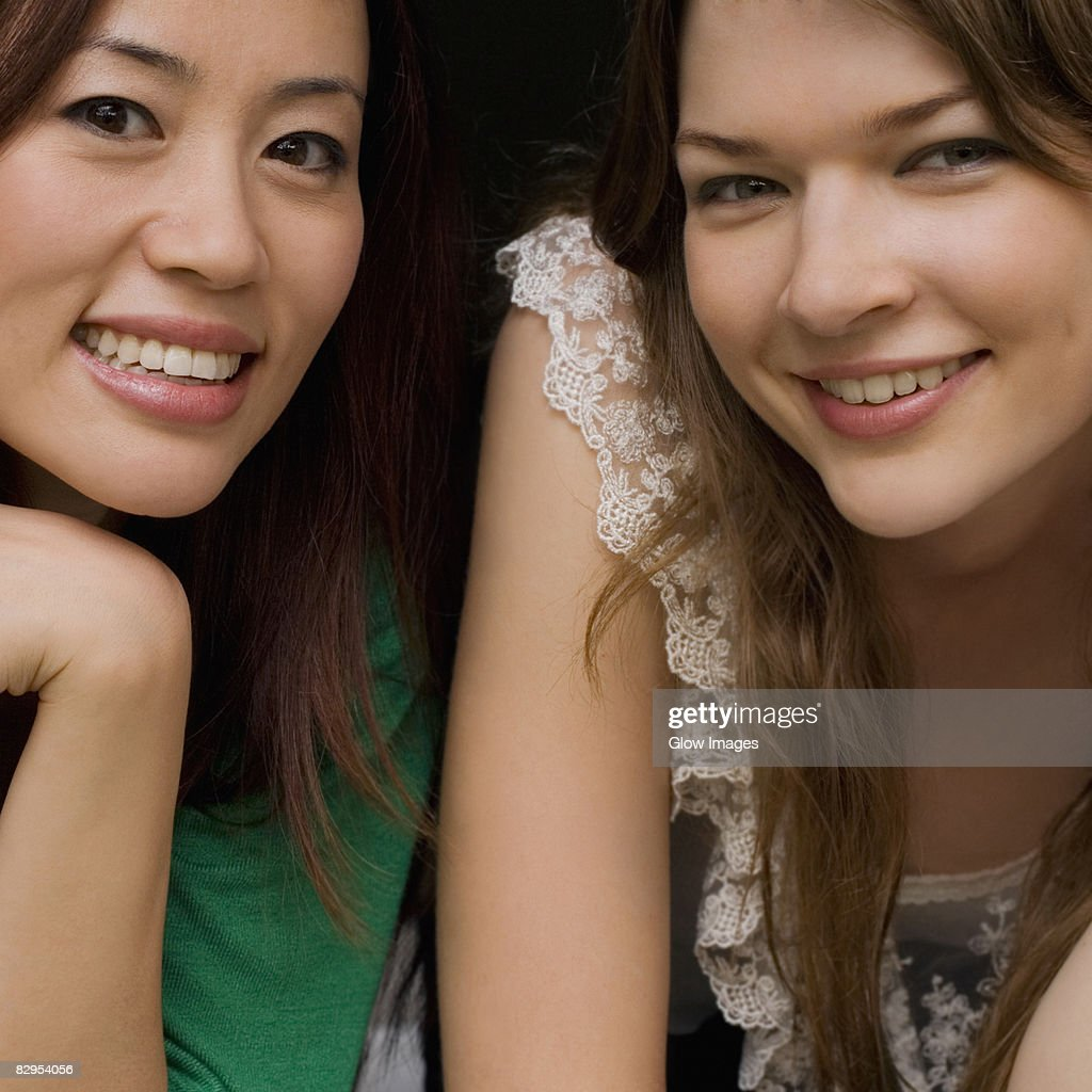 Portrait of two young women smiling together : Stock Photo