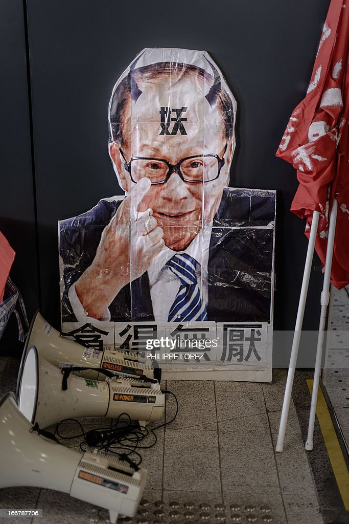 A portrait of tycoon Li Ka-shing is seen next to banners during a protest by dockers on the 21st day of their strike in Hong Kong on April 17, 2013 asking for an increase in pay and better working conditions. The Hong Kong International Terminals (HIT) which operates 12 berths, is a unit of tycoon Li Ka-shing's Hutchison Port Holdings Trust, part of the vast empire owned by Asia's richest man whose firms control about 70 percent of the in the city's port traffic. AFP PHOTO / Philippe Lopez