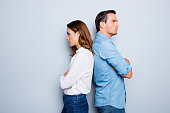 Portrait of unhappy frustrated couple standing back to back not speaking to each other after an argument while standing on grey background. Negative emotion face expression reaction