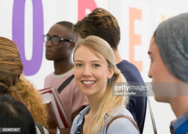 Portrait of university student standing in corridor, students talking in background