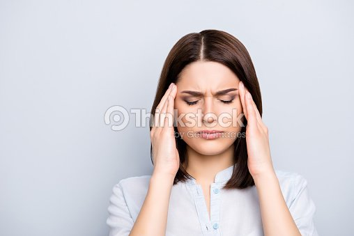 Portrait of upset, sad, pretty, nice, charming, stylish woman in shirt having head ache, stress, troubles, touching temples with fingers and close eyes, standing over grey background : Stock Photo