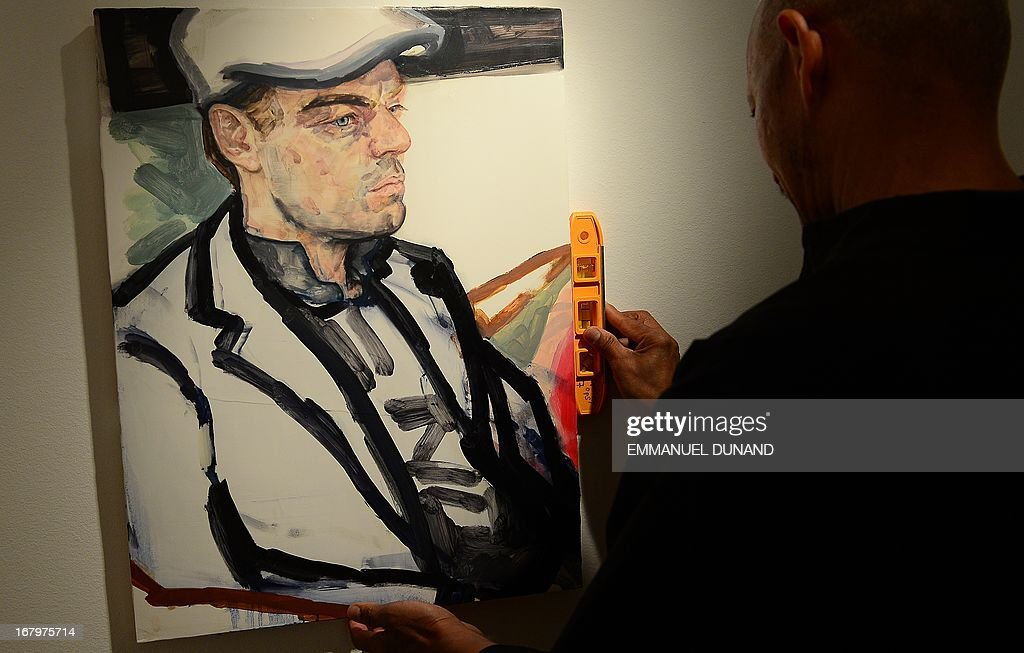 A portrait of US actor Leonardo DiCaprio by artist Elizabeth Peyton is being set up by a Christie's employee ahead of an auction for the 11th Hour charity auction in New York, May 3, 2013. Christie's, in partnership with the Leonardo DiCaprio Foundation will present the 11th Hour charity auction, an evening sale on May 13, 2013 to benefit environmental and wildlife conservation. AFP PHOTO/Emmanuel Dunand MANDATORY MENTION OF THE ARTIST UPON PUBLICATION