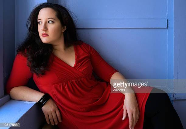 Portrait of Voluptuous Woman Wearing Red Dress and Posing