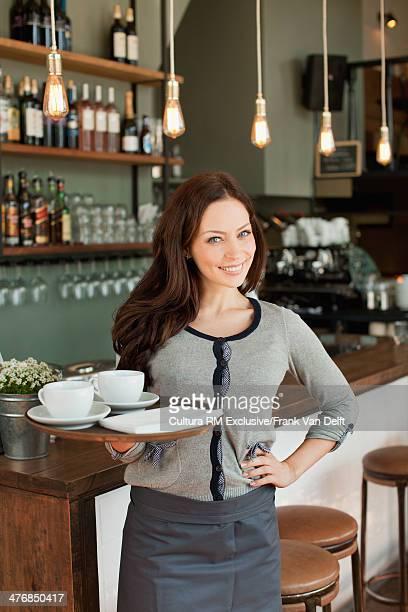 Portrait of waitress holding tray in restaurant