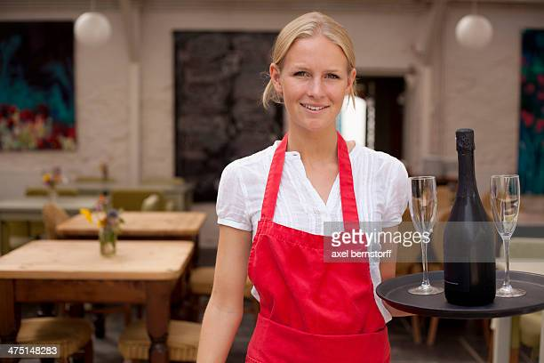 Portrait of waitress with tray of wine and glasses in cafe
