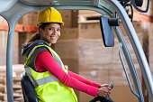 Portrait of warehouse worker using a forklift in warehouse