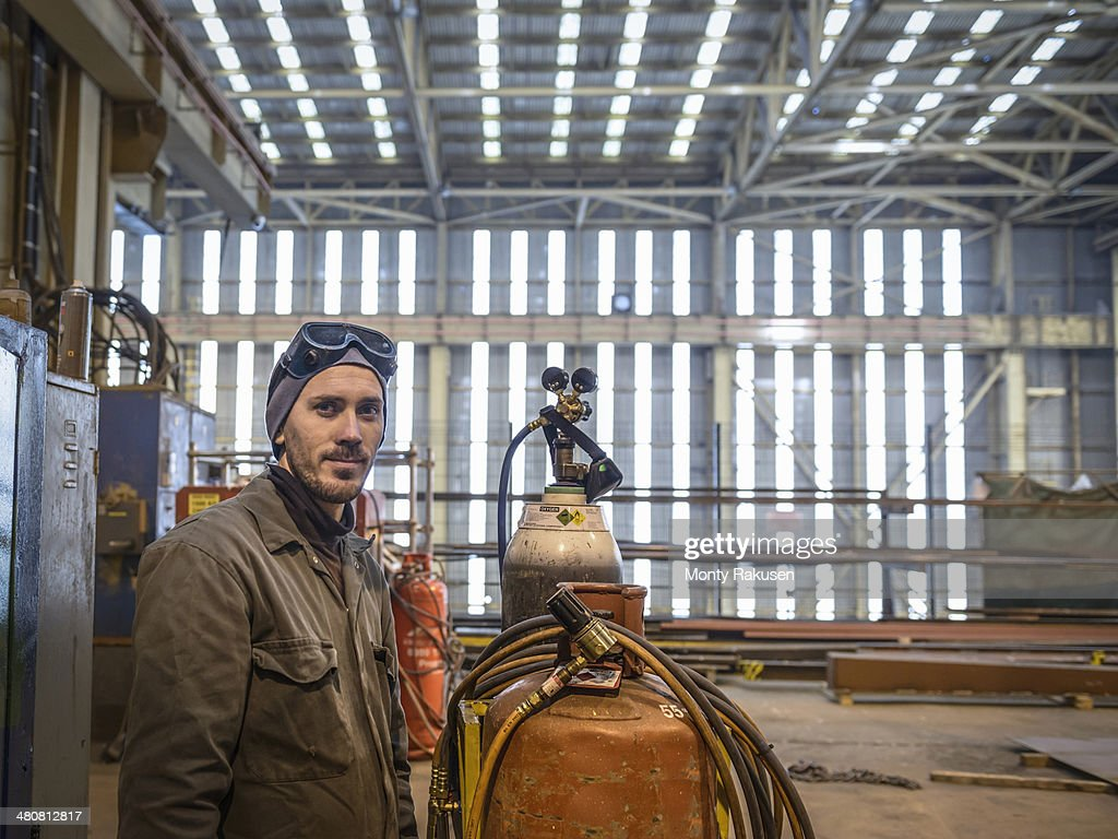 Portrait of welder wearing overalls and safety goggles in factory : Stock Photo