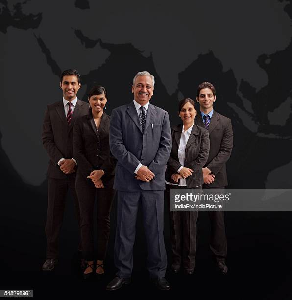 Portrait of well-dressed business people smiling on black background
