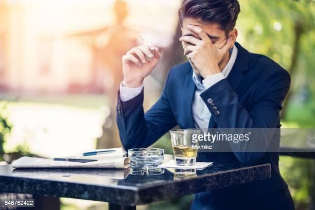 Porträt von gut gekleideten jungen Mann Rauchen und trinken