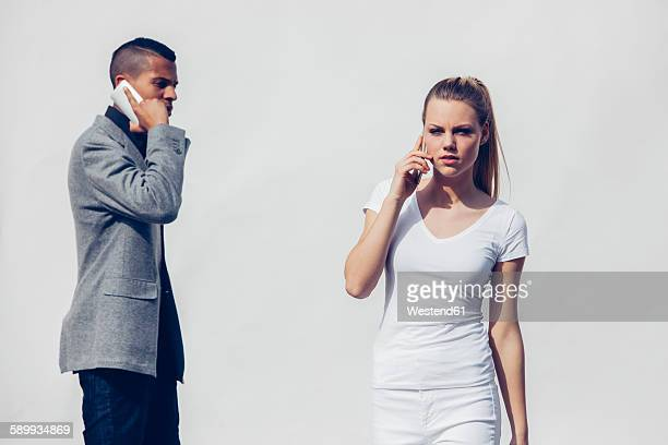 Portrait of white dressed young woman telephoning with smartphone in front of white background