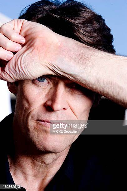 Portrait of Willem Dafoe face with open eyes one arm on the forehead