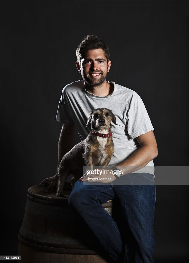 Portrait of winemaker and his dog sitting on wine barrel