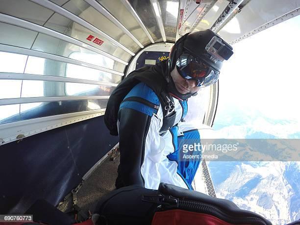 Portrait of wingsuit flier about to jump, plane