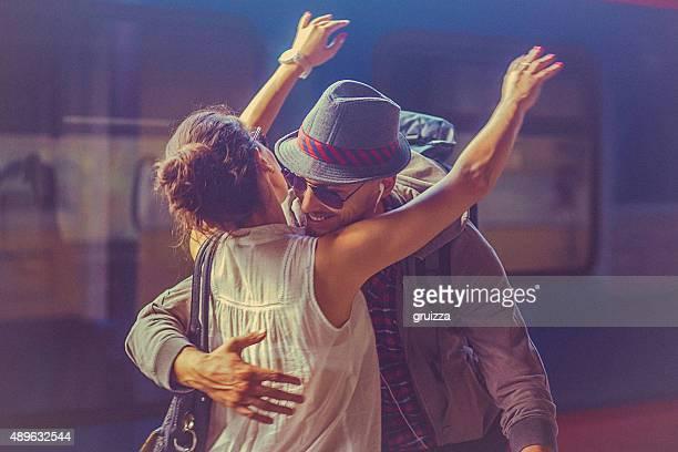 Ritratto di donna e uomo abbracciare sulla piattaforma di stazione ferroviaria