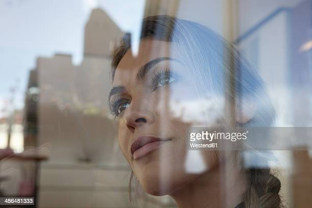 Portrait of woman behind window