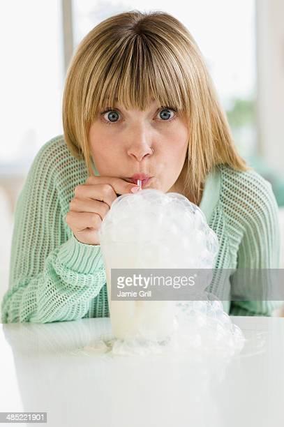Portrait of woman blowing bubbles in milkshake