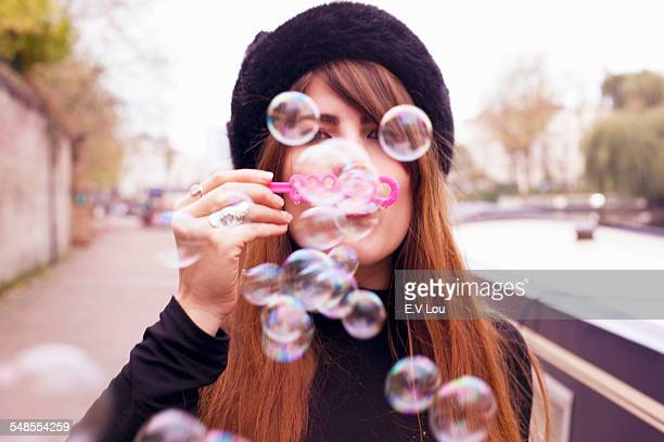 Portrait of woman blowing bubbles