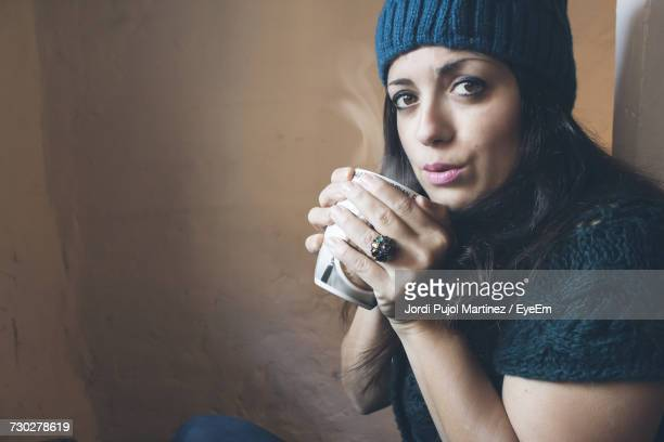 Portrait Of Woman Blowing Hot Coffee While Sitting By Wall