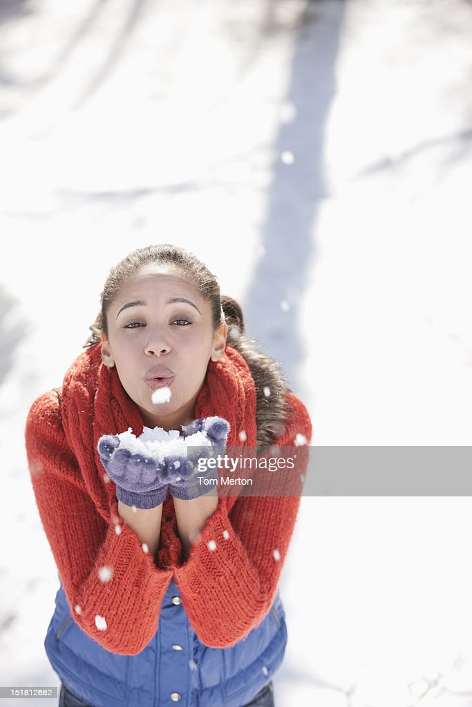 Portrait of woman blowing snow in hands : Stock Photo