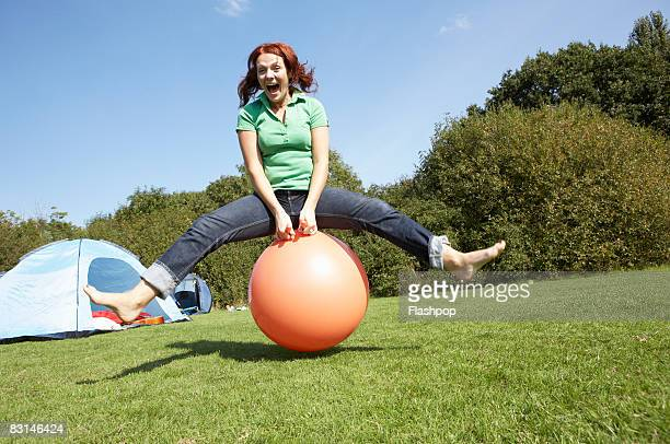 Portrait of woman bouncing on rubber ball