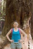Portrait of woman by redwood tree trunk, Felton, California