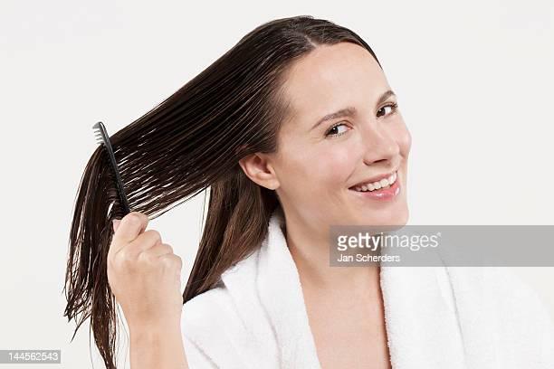 Portrait of woman combing wet hair, studio shot