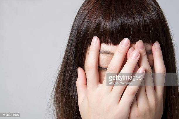 Portrait of woman covering eyes with both hand