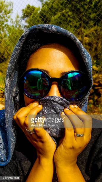 Portrait Of Woman Covering Face With Headscarf While Wearing Sunglasses