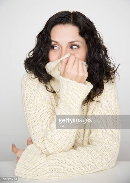 Portrait of woman covering mouth with sweater
