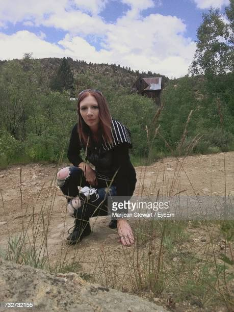 Portrait Of Woman Crouching On Field Against Forest
