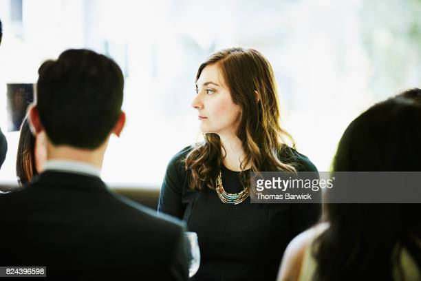 Portrait of woman dining with friends and family in restaurant