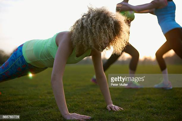 Portrait of woman doing push up exercise in park