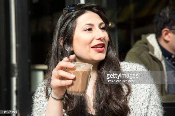 Portrait of woman drinking coffee in urban cafe.