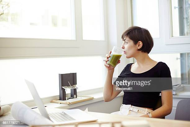 Portrait of woman drinking green smoothie in the office