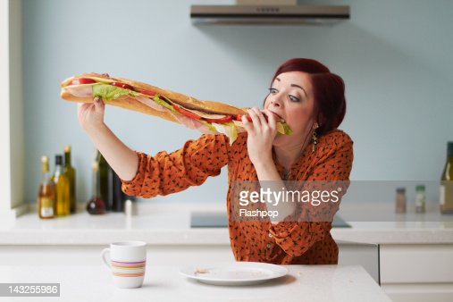 Portrait of woman eating giant baguette : Stock Photo