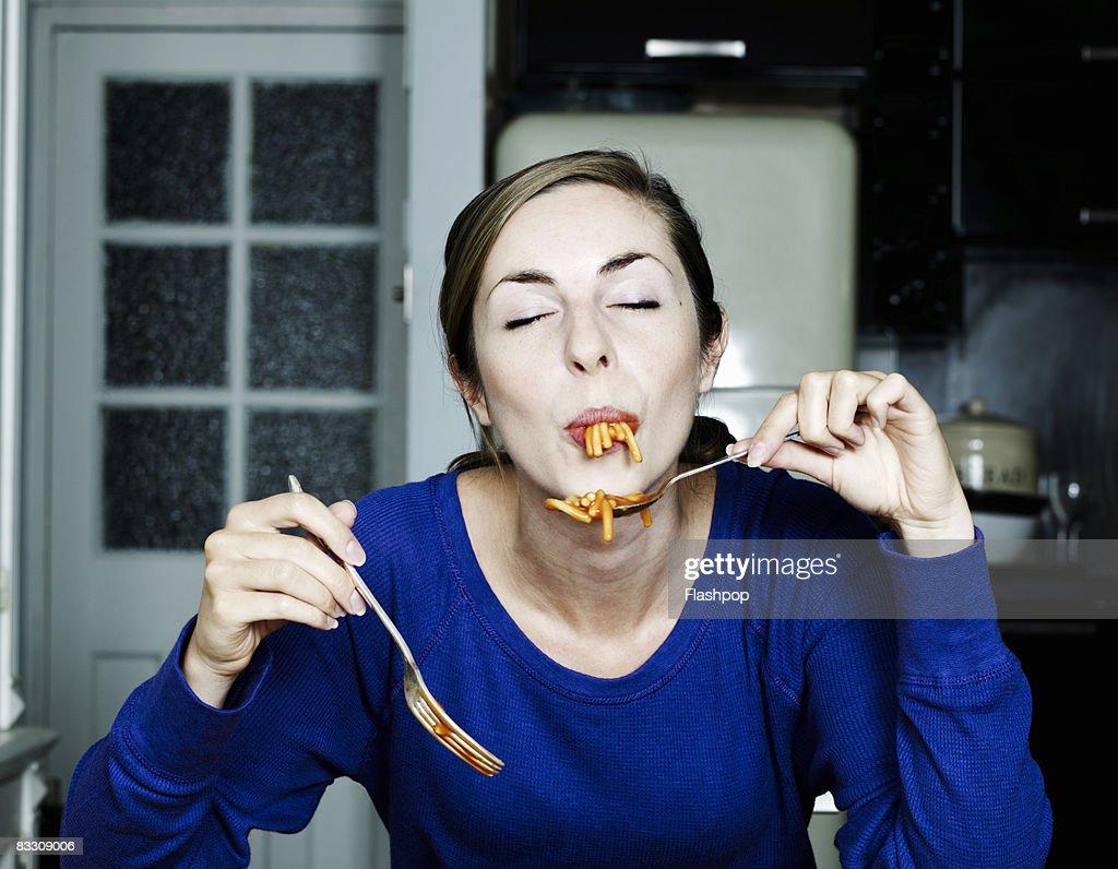 Portrait of woman eating spaghetti