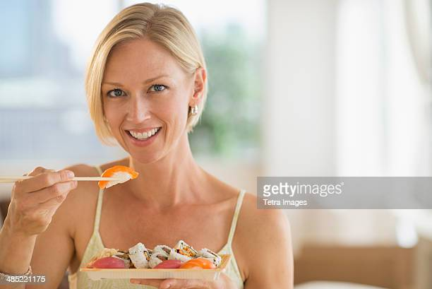 Portrait of woman eating sushi