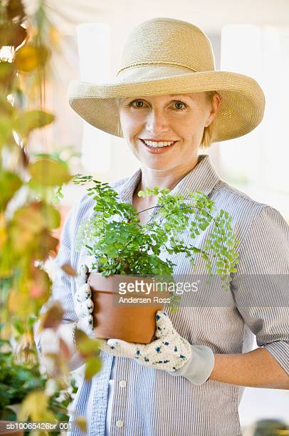 Portrait of woman gardening in conservatory