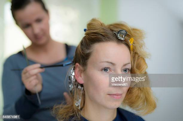 Portrait of woman getting highlights at hairdresser
