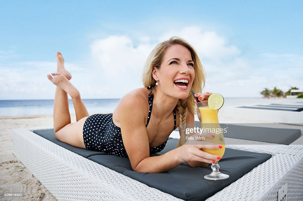 Portrait of woman having drink on deck chair on beach : Stock Photo