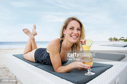Portrait of woman having drink on deck chair on beach : ストックフォト