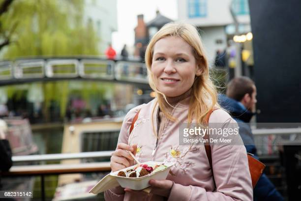 Portrait of woman having take away food in urban farmers market.